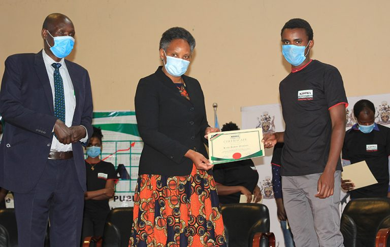 KIPPRA_Board_Member_Dr_Fred_Simiyu_(left),KIPPRA_Executive_Director_Dr_Rose_Ngugi_(centre)_present_certificate_to_a_student