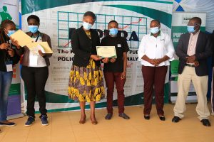 Student_receive_certificate_from_KIPPRA_Executive_Director_Dr_Rose_Ngugi_at_KMPUs_event_in_Kisii_University_JPG